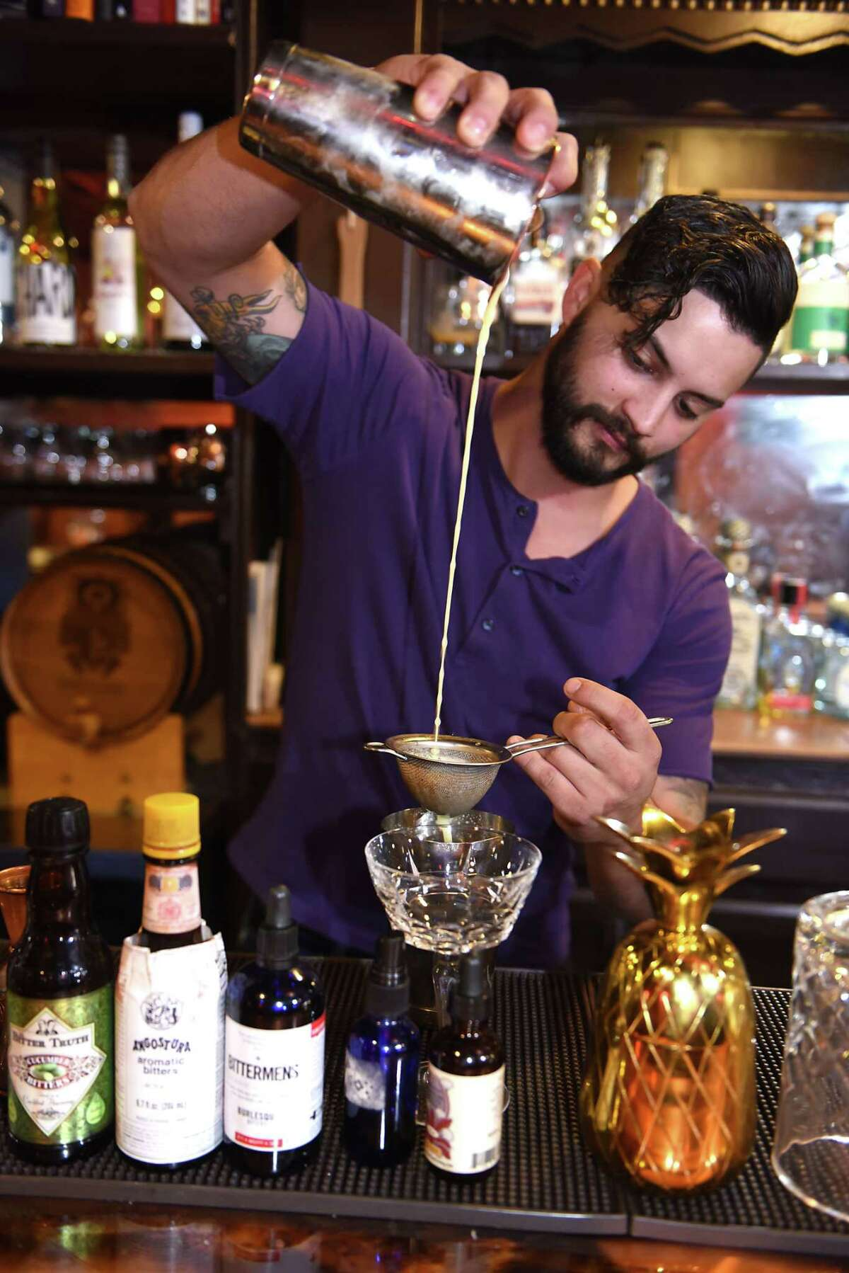 """Bartender George Fiorini makes a cocktail called """"The Jay #2"""" at Savoy Taproom on Thursday, Aug. 17, 2017 in Albany, N.Y. The drink includes 1 oz Mezcal, 1 oz Midori, 3/4 oz sage aquafaba, 3/4 oz lime juice and 1/4 oz cold pressed ginger. (Lori Van Buren / Times Union)"""