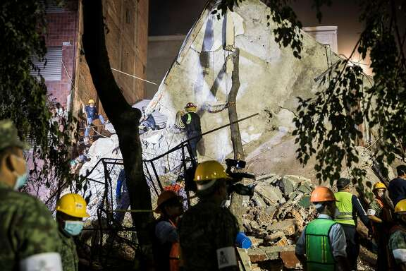 Rescue workers and volunteers search for survivors in the rubble of a building on  Amsterdam Avenue late into the night in the Condesa neighborhood of Mexico City, Sept. 19, 2017. A powerful earthquake struck Mexico Tuesday afternoon, toppling buildings, rattling the capital and sending people flooding into the streets for the second time in just two weeks. Early Wednesday, Mexican officials said on Twitter that at least 216 people had been killed. (Adriana Zehbrauskas/The New York Times)