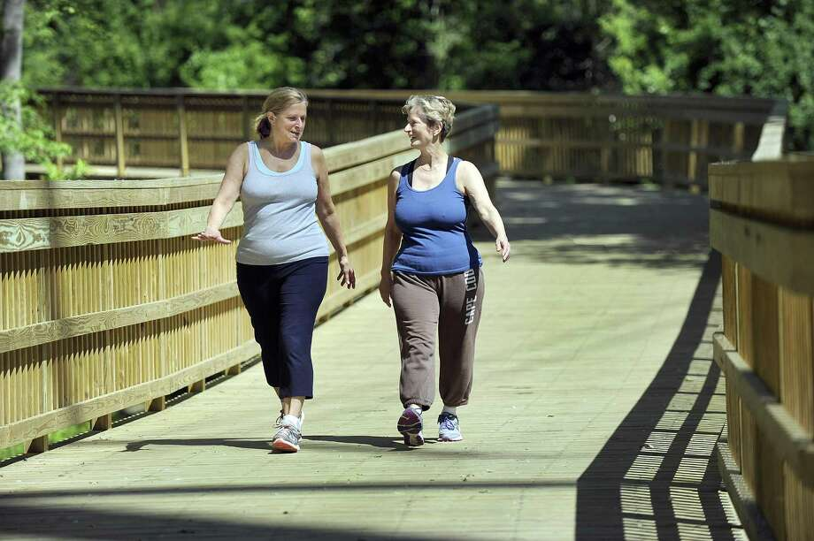 Anita Francisco, left, and her sister, Debbie Clark, go for a walk on the Still River Greenway in Brookfield in June. Photo: Carol Kaliff / Hearst Connecticut Media / The News-Times