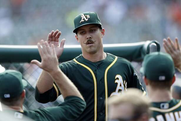 Oakland Athletics starting pitcher Daniel Mengden is greeted in the dugout after the eighth inning of a baseball game against the Detroit Tigers, Wednesday, Sept. 20, 2017, in Detroit. (AP Photo/Carlos Osorio)