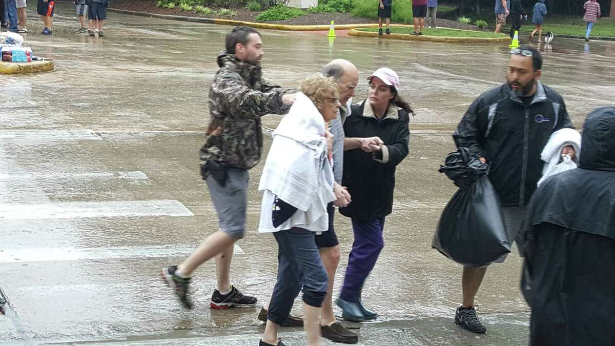 Kingwood residents are evacuated at the West Lake Houston Parkway bridge after being rescued from their flooded homes.