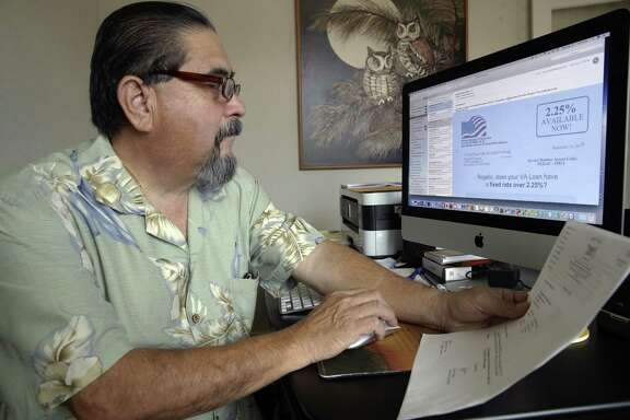 Air Force veteran Roy Ledesma goes over information pertaining to refinancing of his home in San Antonio.