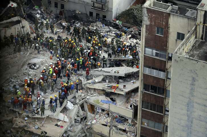 Rescue workers search for people trapped inside a collapsed building in the Del Valle area of Mexico City, Wednesday, Sept. 20, 2017. Mexicans across the city are digging through collapsed buildings, trying to save people trapped in debris under schools, homes and businesses, toppled by a 7.1 earthquake that killed more than 200 people. (AP Photo/Rebecca Blackwell)