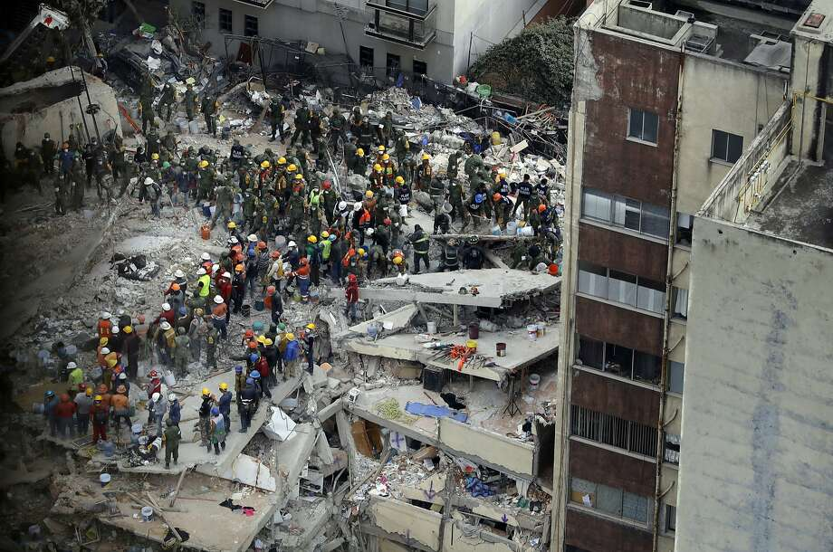 Rescue workers search for people trapped inside a collapsed building in the Del Valle area of Mexico City, Wednesday, Sept. 20, 2017. Mexicans across the city are digging through collapsed buildings, trying to save people trapped in debris under schools, homes and businesses, toppled by a 7.1 earthquake that killed more than 200 people. (AP Photo/Rebecca Blackwell) Photo: Rebecca Blackwell, Associated Press