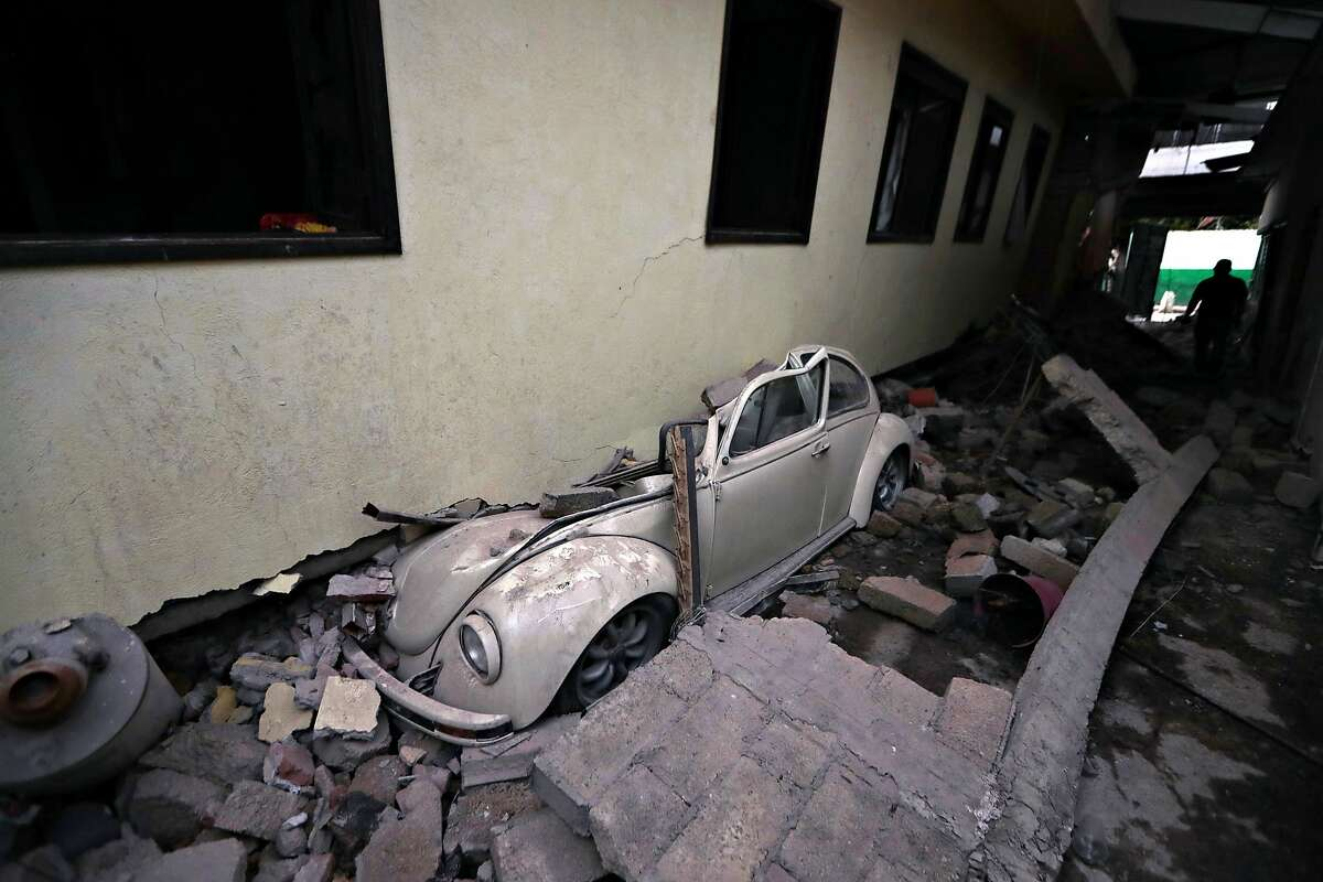 A car sits crushed from a building felled by a 7.1 earthquake, in Jojutla, Morelos state, Mexico, Wednesday, Sept. 20, 2017. Police, firefighters and ordinary Mexicans are digging frantically through the rubble of collapsed schools, homes and apartment buildings, looking for survivors of Mexico's deadliest earthquake in decades as the number of confirmed fatalities climbs. (AP Photo/Eduardo Verdugo)