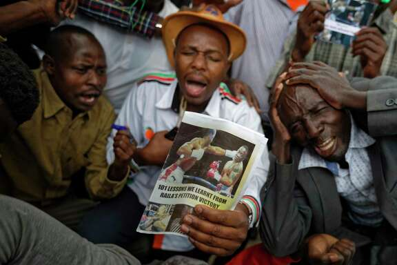 Supporters of opposition leader Raila Odinga hold up a pamphlet showing an artificially-created picture of Odinga, left, knocking out President Uhuru Kenyatta, right, as they demonstrate outside the Supreme Court in downtown Nairobi, Kenya Wednesday, Sept. 20, 2017. In a detailed ruling issued Wednesday the court said it nullified President Uhuru Kenyatta's re-election largely because the electoral commission refused scrutiny of its computerized voting system. (AP Photo/Ben Curtis)