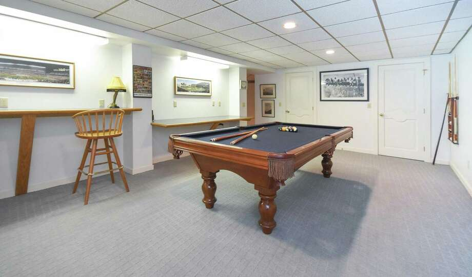 The lower level contains a play or game room with built-in counter space along one wall.