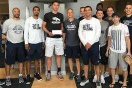 Quentin Millora-Brown (center), poses with Rice basketball players and coaches.