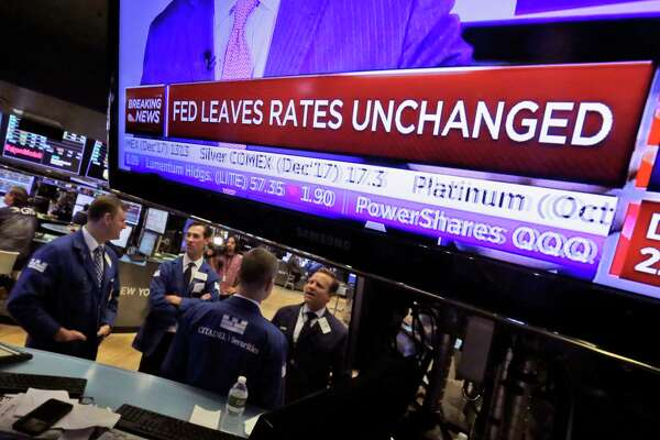 The rate decision by  the Federal Reserve appears Wednesday on a TV screen at the New York Stock Exchange.