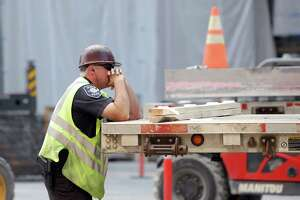 A Seattle Police officer works off-duty construction detail as crews work on building projects near 9th Avenue and Stewart Street in downtown Seattle, Tuesday, Aug. 29, 2017.