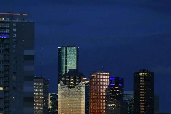 Cyclists stop to photograph the downtown Houston skyline shortly after sunset  (Mark Mulligan / Houston Chronicle)
