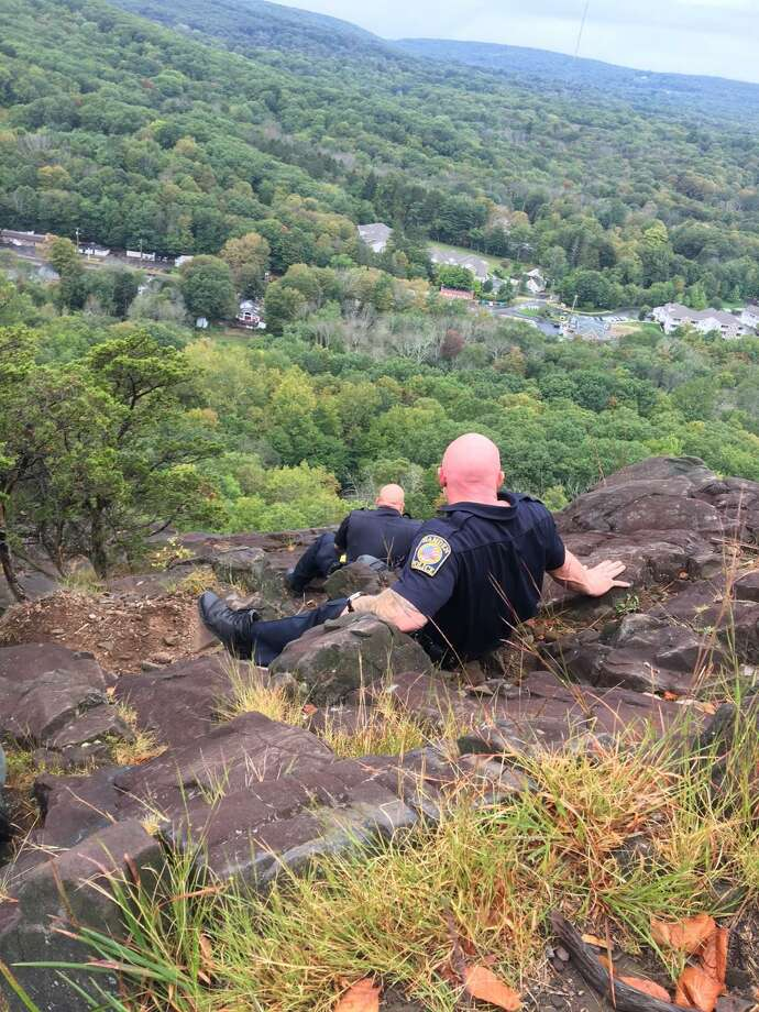Hamden Police officers Paul Calamita and Timothy Mckeon on Sleeping Giant mountain talking to a distraught woman sitting at the edge of the cliff. Photo: Contributed Photo/Hamden Police