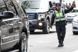 A Seattle traffic officer directs cars out of a parking garage at  3rd Ave and Spring St. during the evening commute on Wednesday, Sept. 20, 2017.