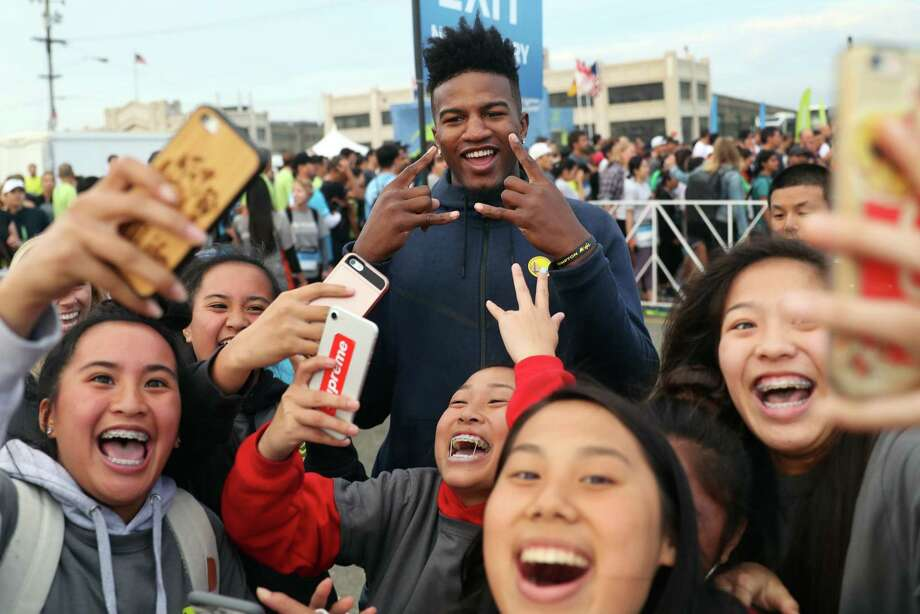 J.P. Morgan Corporate Challenge 5K volunteers take selfies with Golden State Warriors' rookie Jordan Bell in San Francisco, Calif., on Thursday, September 7, 2017. Photo: Scott Strazzante / The Chronicle / San Francisco Chronicle