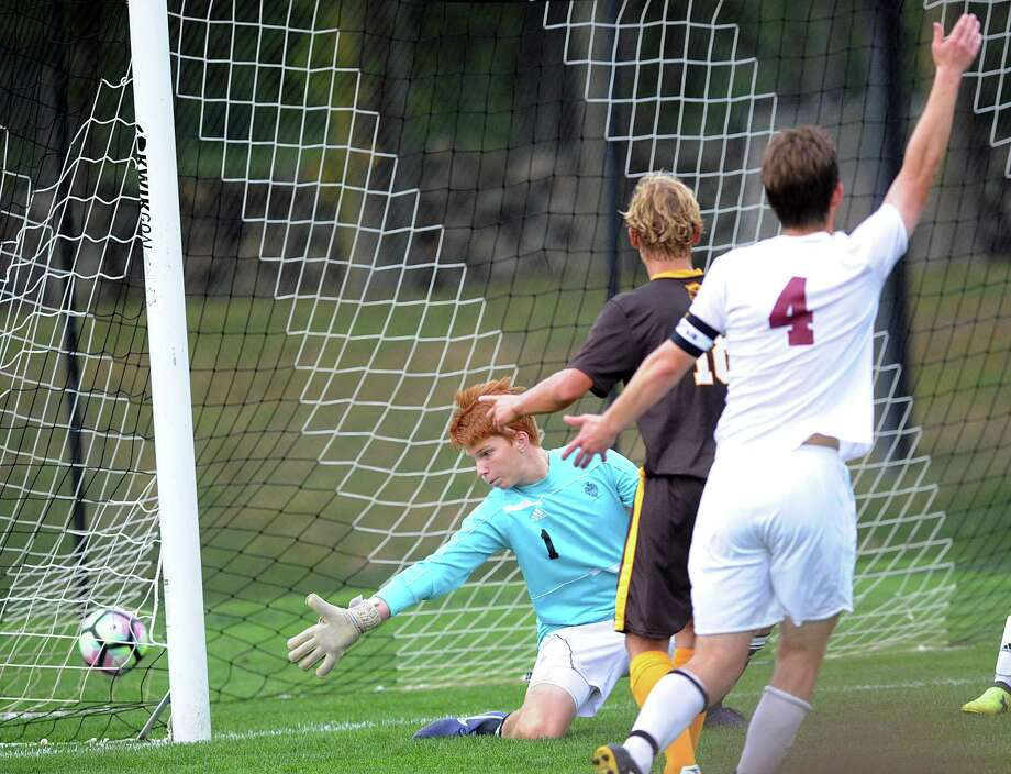 At center, Henry Foster of Brunswick looks on as his shot  beats Loomis Chaffee goalkeeper Jamie Fite, left, for a first-half goal during the boys high school soccer match between Brunswick School and Loomis Chaffee School at Brunswick in Greenwich, Conn., Wednesday, Sept. 20, 2017. At far right trailing the play is Aidan O'Brien (#4) of Loomis Chaffee. Photo: Bob Luckey Jr. / Hearst Connecticut Media / Greenwich Time