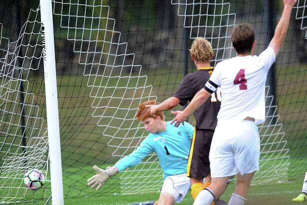 At center, Henry Foster of Brunswick looks on as his shot  beats Loomis Chaffee goalkeeper Jamie Fite, left, for a first-half goal during the boys high school soccer match between Brunswick School and Loomis Chaffee School at Brunswick in Greenwich, Conn., Wednesday, Sept. 20, 2017. At far right trailing the play is Aidan O'Brien (#4) of Loomis Chaffee.