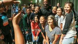 Former NFL player Priest Holmes poses for a photo with a group of happy students in the Southwest High School auditorium Tuesday after he, former NFL player and coach Rance Olison and former baseball player Dick O'Neal gave timely advice to the students about succeeding in life.