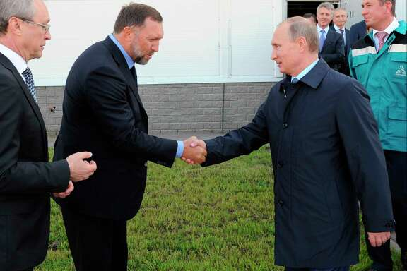 Russian President Vladimir Putin, right, shakes hands with Russian metals mogul Oleg Deripaska, whom President Donald Trump's former campaign chairman, Paul Manafort, secretly worked with a decade ago to advance Putin's interests.