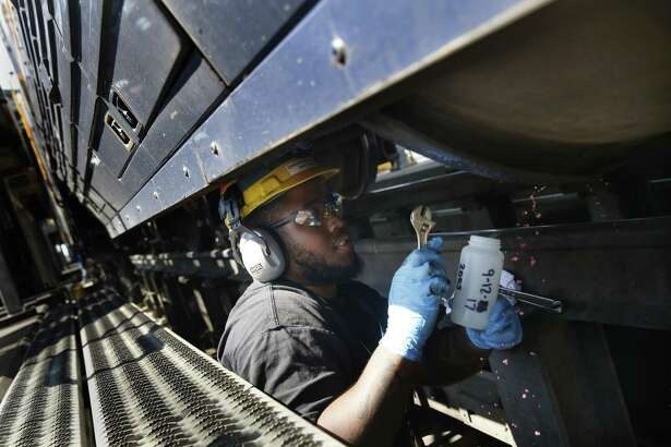 Amtrak machinist, Darrion Brown, takes a sample of renewable diesel from the fuel tank on a Capital Corridor locomotive for the testing of contaminants, degradation and for quality standards measures at the Amtrak Maintenance Facility in Oakland on Tuesday, September 12, 2017.