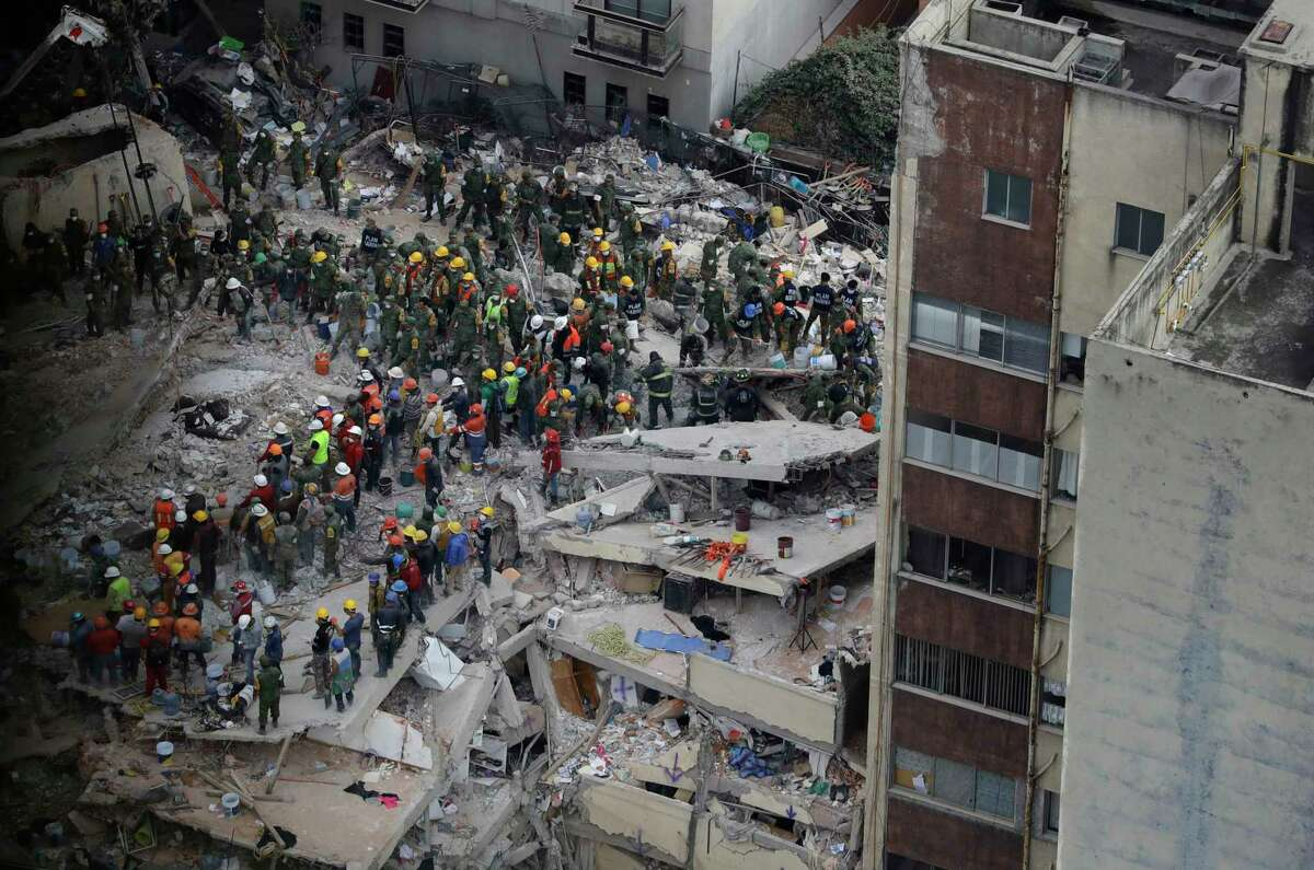 Rescue workers search for people trapped inside a collapsed building felled by a 7.1 magnitude earthquake in the Del Valle area of Mexico City, Wednesday, Sept. 20, 2017. Tuesday's magnitude-7.1 quake struck on the 32nd anniversary of the 1985 earthquake that killed thousands. Just hours before it hit, people around Mexico had held earthquake drills to mark the date. (AP Photo/Rebecca Blackwell) ORG XMIT: XLAT103