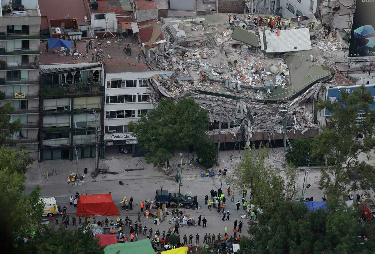 Rescue workers search for people trapped inside a collapsed building in the Roma Norte neighborhood of Mexico City, Wednesday, Sept. 20, 2017. Mexicans across the city are digging through collapsed buildings, trying to save people trapped in debris under schools, homes and businesses, toppled by a 7.1 earthquake that killed more than 200 people. (AP Photo/Rebecca Blackwell) ORG XMIT: RLB114
