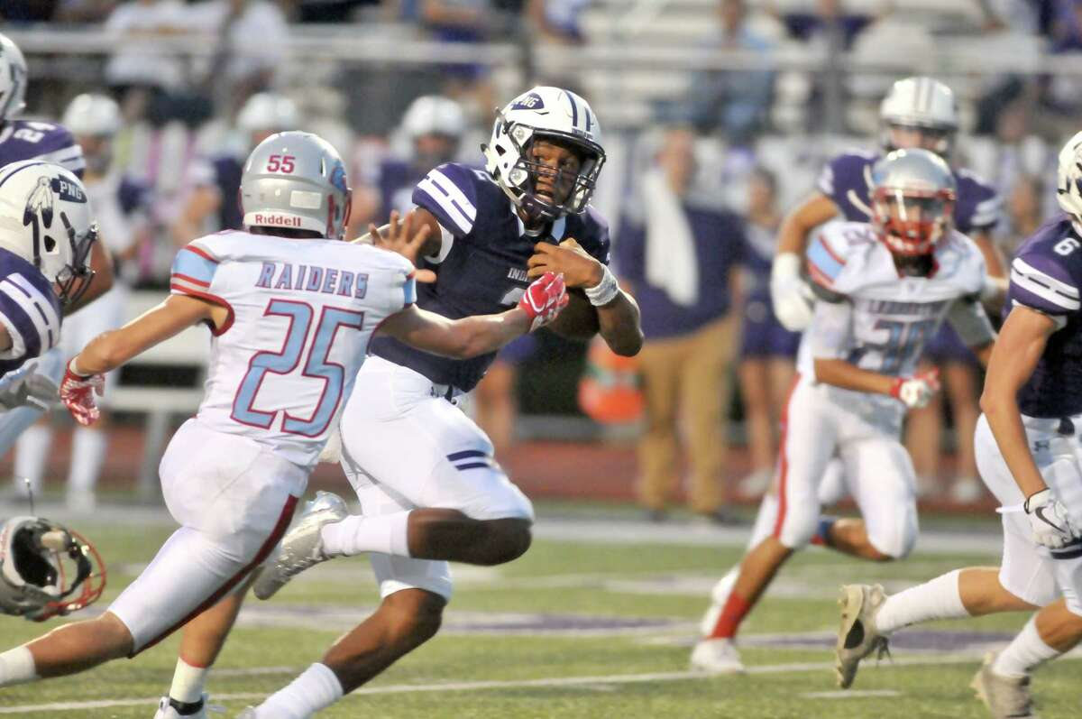 Port Neches-GrovesÂ?' Roschon Johnson reaches out to fend of LumbertonÂ?'s Weston Tinlsey as the Indians drive toward their end zone in the first half of WednesdayÂ?'s game at Indian Stadium in Port Neches. (Mike Tobias/The Enterprise)