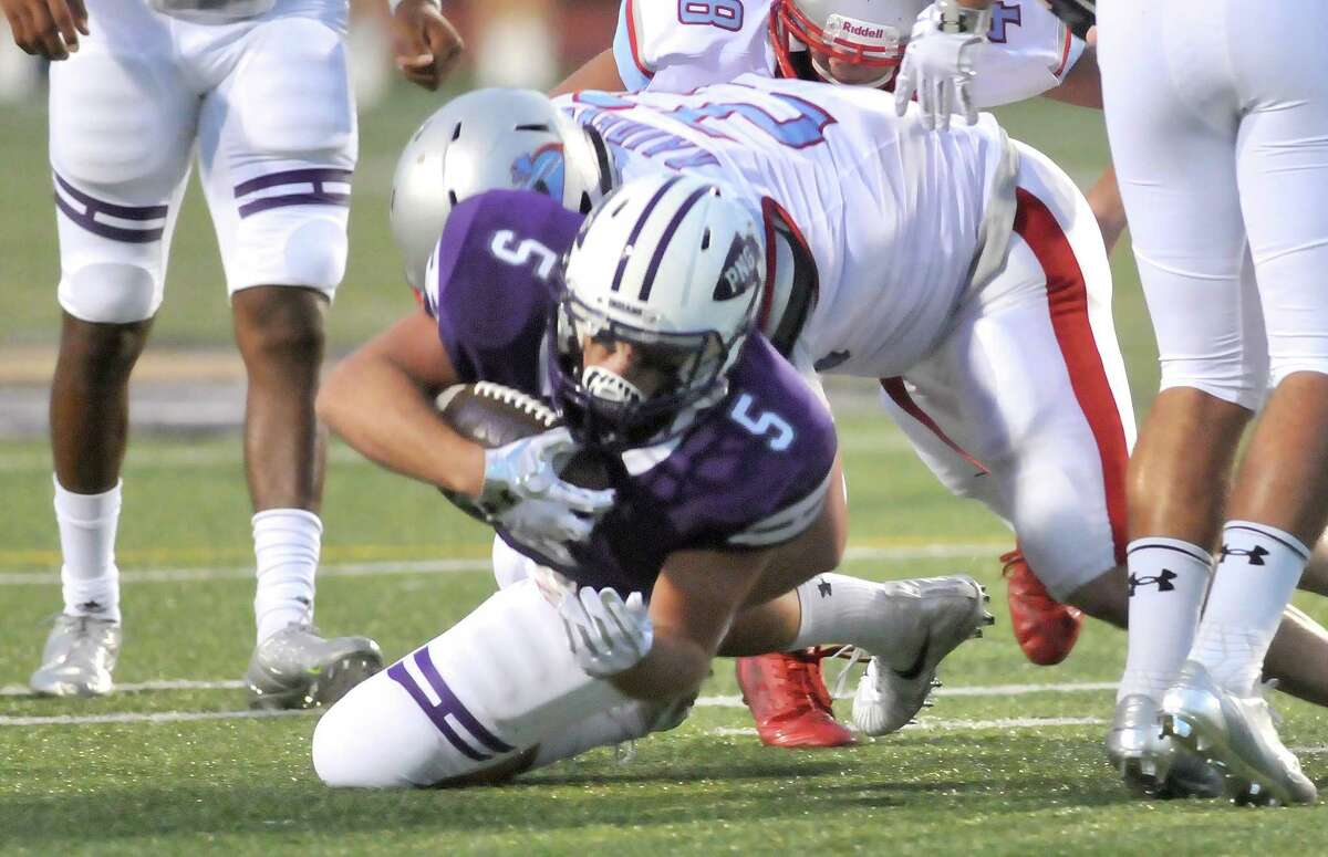 Port Neches-GrovesÂ?' Gavin Deslatte is brought down by a pair of Lumberton defenders as the Indians drive toward their end zone in the first half of WednesdayÂ?'s game at Indian Stadium in Port Neches. (Mike Tobias/The Enterprise)