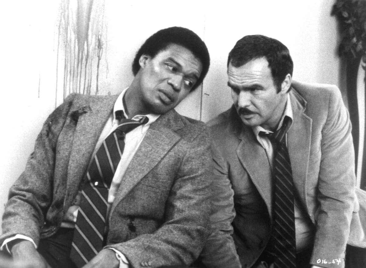 CIRCA 1981: Actors Bernie Casey and Burt Reynolds on set of the movie