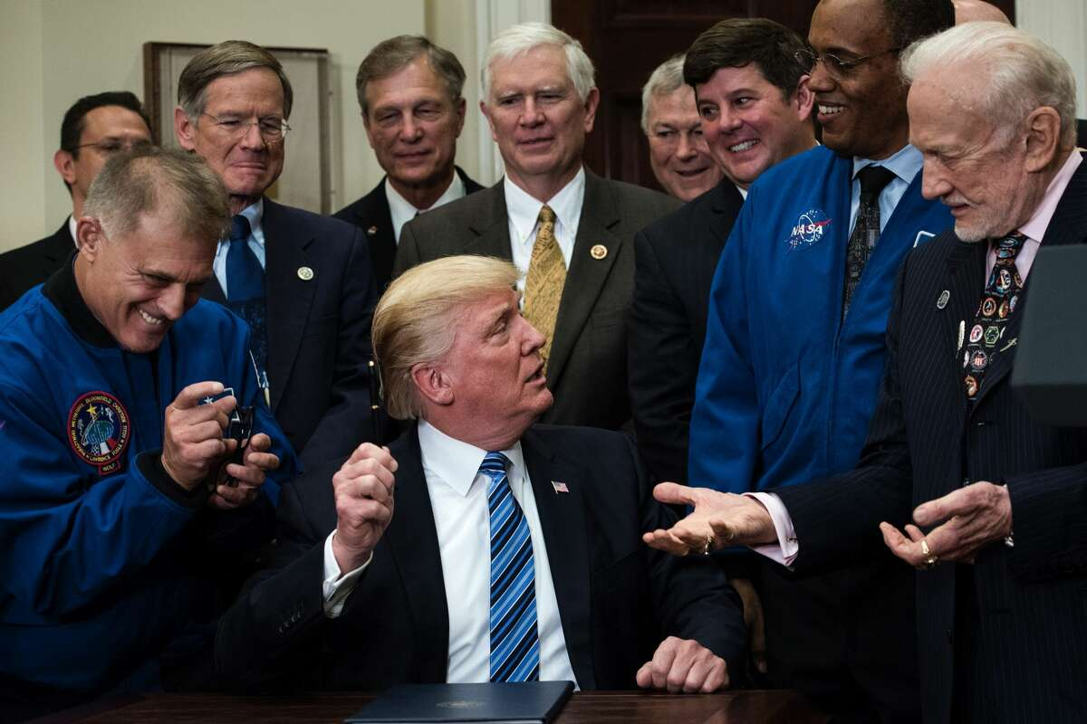 David Wolf (L), former NASA astronaut, pretends to take a pen from US President Donald Trump (C) as her presents it to Buzz Aldrin, former NASA Astronaut and second man on the moon, after signing an executive order about space exploration in the Roosevelt Room at the White House June 30, 2017 in Washington, DC. / AFP PHOTO / Brendan Smialowski (Photo credit should read BRENDAN SMIALOWSKI/AFP/Getty Images)