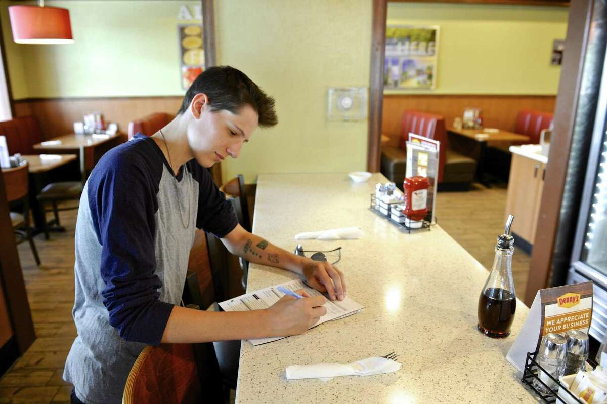 A job applicant fills paperwork in August 2017 at Denny's in Danbury, Conn. Online job postings were down 13 percent in the Danbury area in August from a year earlier, contributing to an overall 5 percent drop in southwestern Connecticut as calculated by The Conference Board.