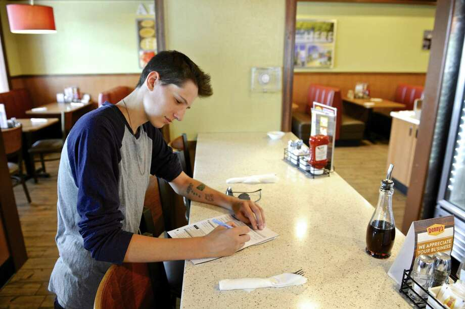 A job applicant fills paperwork in August 2017 at Denny's in Danbury, Conn. Online job postings were down 13 percent in the Danbury area in August from a year earlier, contributing to an overall 5 percent drop in southwestern Connecticut as calculated by The Conference Board. Photo: H John Voorhees III / Hearst Connecticut Media / The News-Times