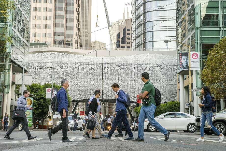 Pedestrians cross the street with the Transbay Transit Center under construction in the background. The terminal is likely to open in June, but some buses on the 5-Fulton route will use the hub starting Dec. 26. Photo: Santiago Mejia, The Chronicle