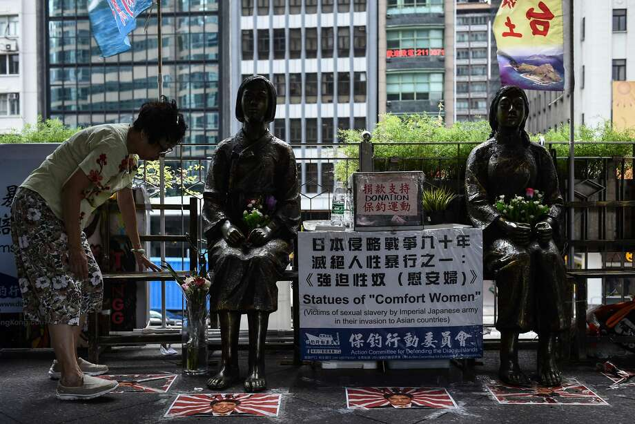 "A woman places flowers Monday next to Hong Kong statues of ""comfort women,"" or sex slaves. Photo: ANTHONY WALLACE, AFP/Getty Images"