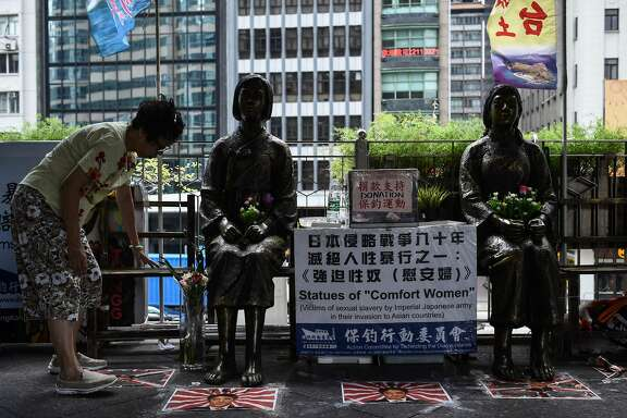 """A woman places flowers next to two """"comfort women"""" statues ahead of a protest to mark the 86th anniversary of the 'Mukden Incident' in Hong Kong on September 18, 2017.     The 'Mukden Incident' took place in 1931, when Japanese soldiers blew up a railway in Manchuria as a pretext to take control of the entire northeastern region a few years before the outbreak of World War II.    / AFP PHOTO / Anthony WALLACEANTHONY WALLACE/AFP/Getty Images"""