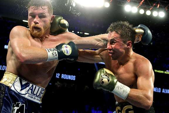 Gennady Golovkin (right) exchanges blows with Canelo Alvarez (L) during their WBC, WBA and IBF middleweight championship fight at the T-Mobile Arena on Sept. 16, 2017 in Las Vegas.