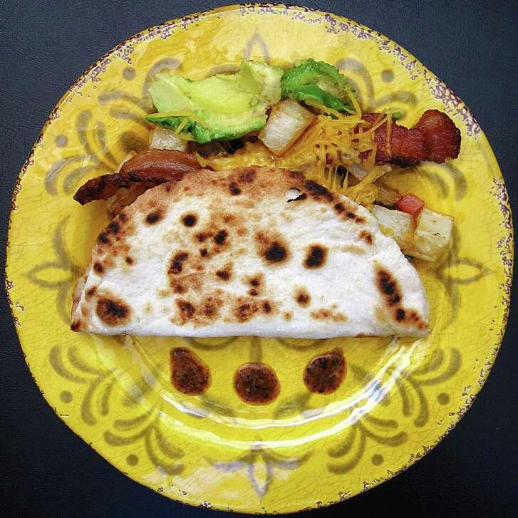 Taco Bañado with bacon, potatoes, pico de gallo, avocado and cheese on a toasted, handmade flour tortilla from Lil' Jonny's Taco House.