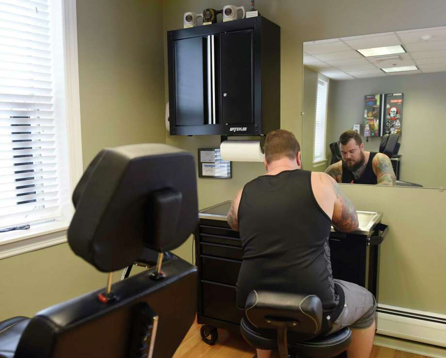 Doug Kapareiko, owner of Borough Six Gallery, works on a tattoo design at his studio in the Byram section of Greenwich, Conn. Thursday, Aug. 21, 2017. Byram businesses have noticed a parking shortage downtown, largely resulting from Port Chester employees parking in the free Byram municipal lot and then getting a ride or walking over to Port Chester. Photo: Tyler Sizemore, Hearst Connecticut Media / Greenwich Time