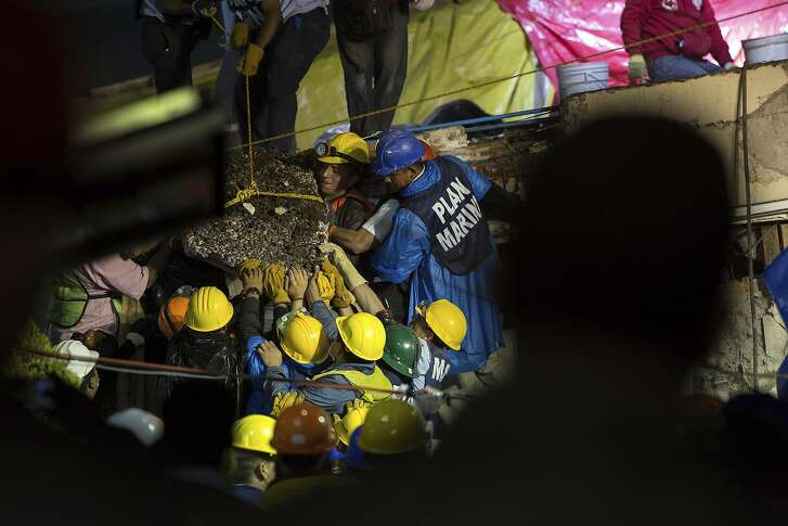 Search and rescue team members work to bring down a large piece of concrete during rescue efforts at the Enrique Rebsamen school in Mexico City, Mexico, Thursday, Sept. 21, 2017. A delicate effort to reach a young girl buried in the rubble of the school stretched into a new day on Thursday, a vigil broadcast across the nation as rescue workers struggled in rain and darkness to pick away unstable debris and reach her.  (AP Photo/Anthony Vazquez)