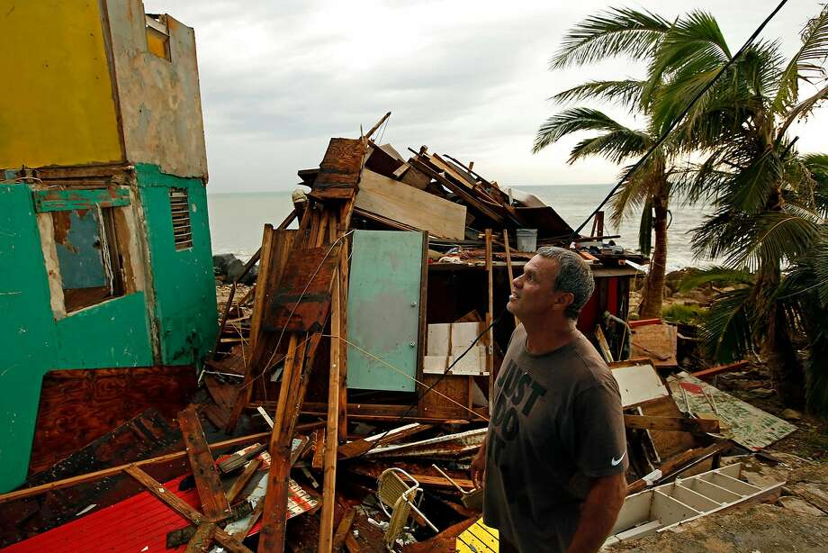 Ivan Lopez looks at the damage to his neighbors' homes in San Juan after Hurricane Maria ravaged Puerto Rico. It could be months before power is restored to the U.S. territory. Photo: Carolyn Cole, TNS