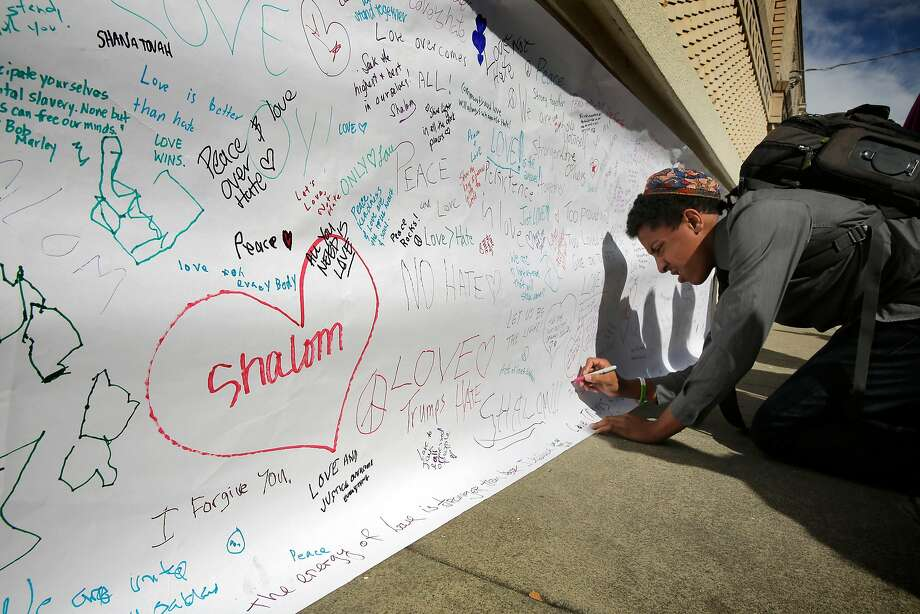 Eric Getreuer, 16, writes a positive message on paper covering up anti-Semitic graffiti at Temple Sinai in Oakland. Photo: Michael Macor, The Chronicle