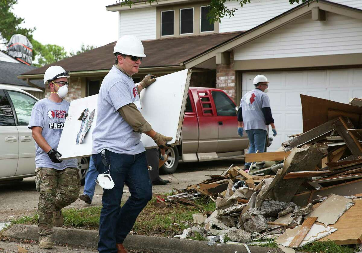 Sen. Ted Cruz, second left, and a Team Rubicon Disaster Response member help clean out the Harvey-damaged Garcia house on Lucian Lane Thursday, Sept. 21, 2017, in Friendswood, Texas. Cruz was along a group of Congressional delegation, including House Speaker Paul Ryan, to assist Team Rubicon, a non-profit organization that pairs military veterans with first responders to deploy emergency response teams, with relief efforts in the neighborhood. ( Yi-Chin Lee/Houston Chronicle via AP)