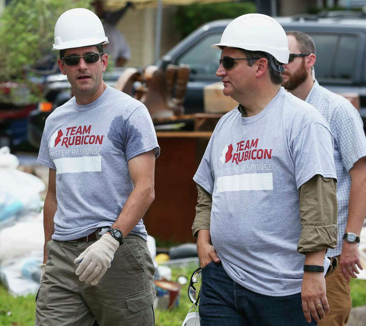 House Speaker Paul Ryan, from left, Sen. Ted Cruz, and a group of Congressional delegates arrive at the Garcia house on Lucian Lane to assist Team Rubicon Disaster Response to clean out the Garcias' Harvey-damaged house Thursday, Sept. 21, 2017, in Friendswood. Team Rubicon is a non-profit organization that pairs military veterans with first responders to deploy emergency response teams. ( Yi-Chin Lee/Houston Chronicle via AP)