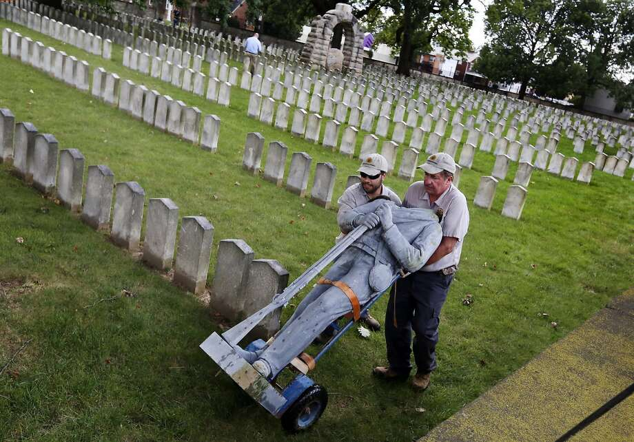 Bert Cambron, left, and Mark Wilson employees of Dayton National Cemetery move the vandalized Confederate soldier statue that stood in Camp Chase Confederate Cemetery on Tuesday, Aug. 22, 2017, in Columbus, Ohio. Columbus police say vandals appear to have climbed on an arched memorial at Camp Chase Confederate Cemetery and toppled the statue atop the monument to the ground. The soldier's head and hat were knocked off. Police say the vandals took the head but left the hat. (Eric Albrecht/The Columbus Dispatch via AP) Photo: Eric Albrecht, Associated Press