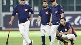 Astros players (from right) Carlos Correa, Alex Bregman and Jose Altuve and manager A.J. Hinch watch batting practice before a game against the Chicago White Sox at Minute Maid Park on Sept. 19, 2017, in Houston.