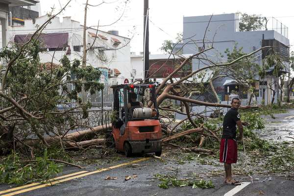 "SAN JUAN, PUERTO RICO - SEPTEMBER 21: Residents begin to clean up the day after Hurricane Maria made landfall, on September 21, 2017 in San Juan Puerto Rico. The majority of the island has lost power, in San Juan many are left without running water or cell phone service, and the Governor said Maria is the ""most devastating storm to hit the island this century."" (Photo by Alex Wroblewski/Getty Images)"