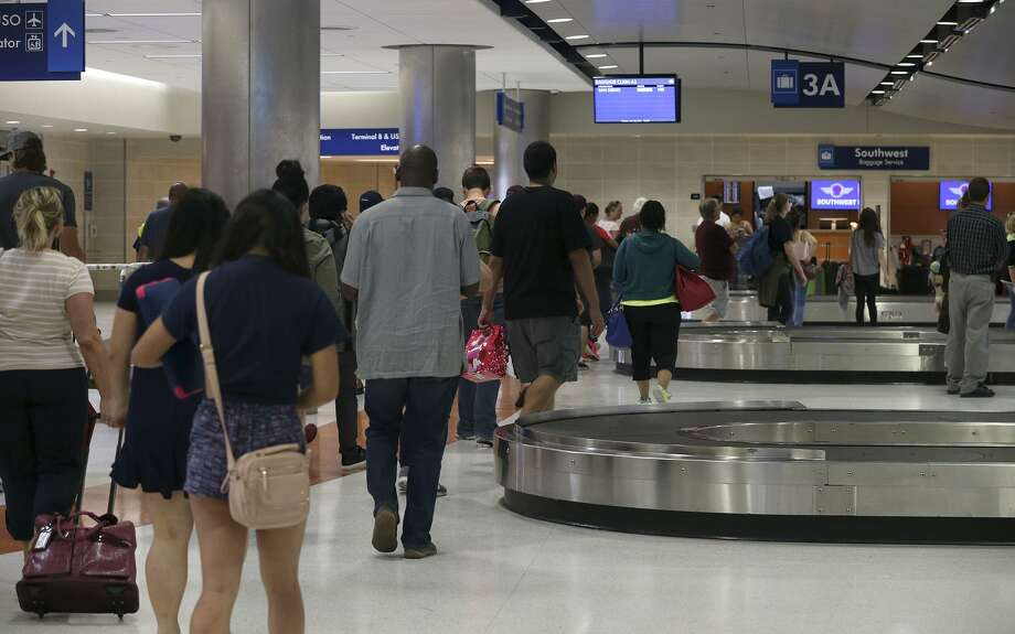 Travelers wait for their luggage after arriving at the San Antonio International Airport in 2015. The airport received a mixed customer satisfaction ranking in the latest J.D. Power survey measuring customer satisfaction at U.S. airports. Photo: San Antonio Express-News File Photo / ©San Antonio Express-News/John Davenport
