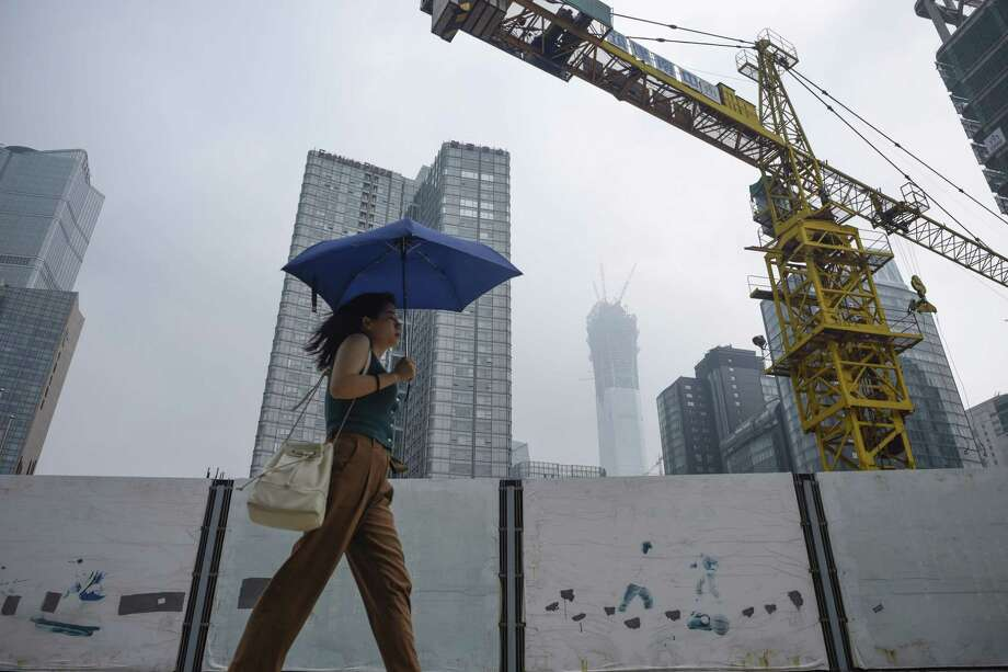 "A woman holds an umbrella as she walks past a construction site in Beijing in August. Standard & Poor's slashed China's credit rating on Thursday, warning that a prolonged period of debt growth had raised ""economic and financial risks. Photo: Wang Zhao /AFP /Getty Images / AFP or licensors"