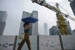 """A woman holds an umbrella as she walks past a construction site in Beijing in August. Standard & Poor's slashed China's credit rating on Thursday, warning that a prolonged period of debt growth had raised """"economic and financial risks."""