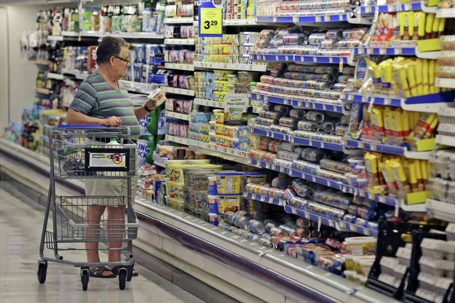 A shopper looks at an item in the dairy section of a Kroger grocery store in Richardson in 2014. Some of the world's biggest consumer goods companies have agreed to simplify food date labels that create confusion among shoppers and leads them to discard billions of dollars worth of food. Photo: Associated Press File Photo / AP2014