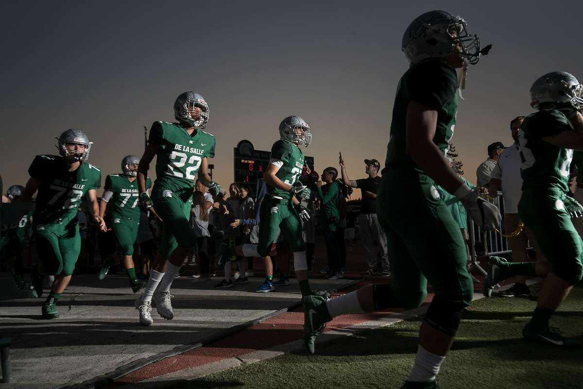 De La Salle Easton Elting (72), De La Salle Nick Ratinho (77), De La Salle Amir Wallace (22), De La Salle Grant Daley (37) and others enter the field to play against St. Francis at De La Salle High School on Friday, Sept. 8, 2017 in Concord, CA.